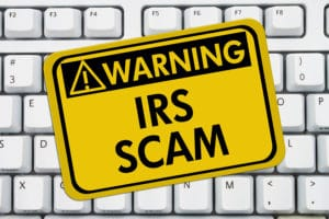 IRS Scam Warning Sign A yellow sign with the words IRS Scam on a keyboard